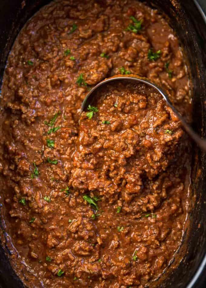 stirring beef ragu in a slow cooker
