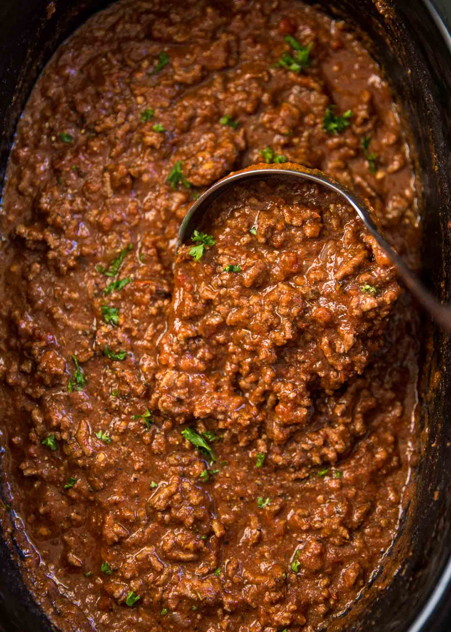 classic beef sauce in a slow cooker with a ladle