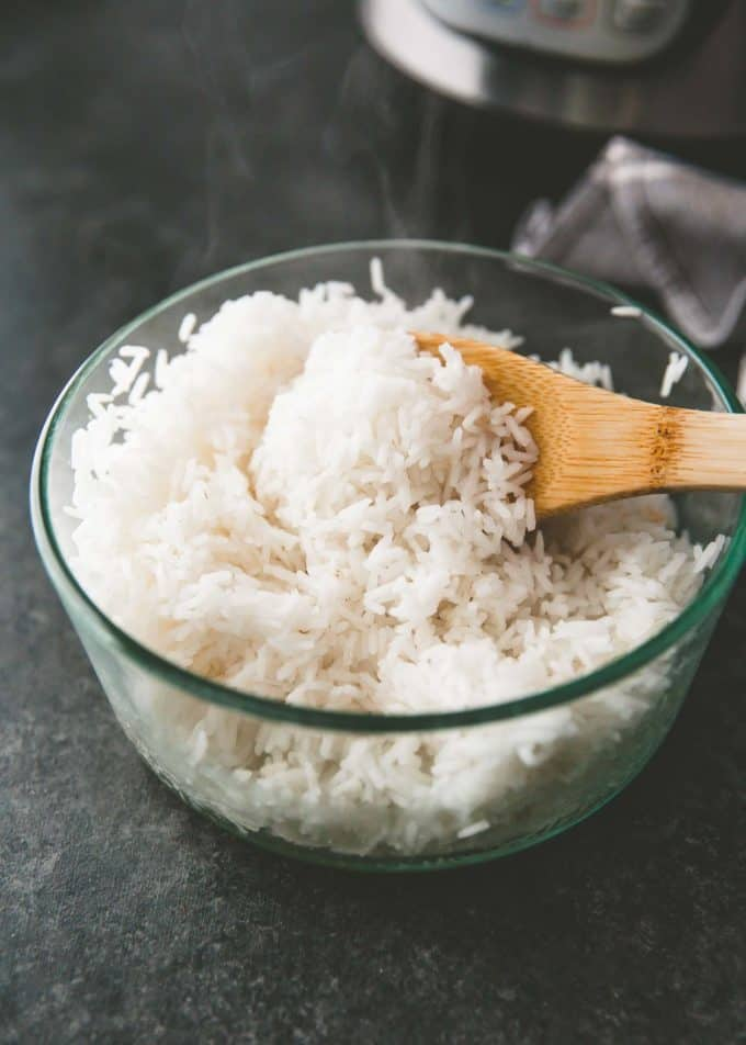 rice in a clear dish with a wooden spoon