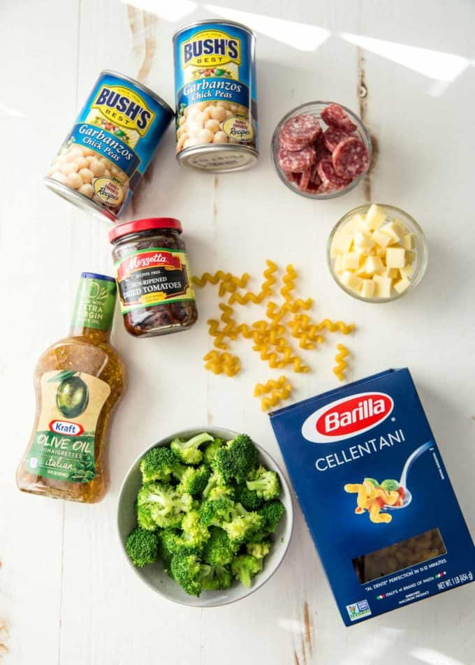 garbanzo beans, vinaigrette, roasted tomatoes, broccoli, pasta and cheese on a white table