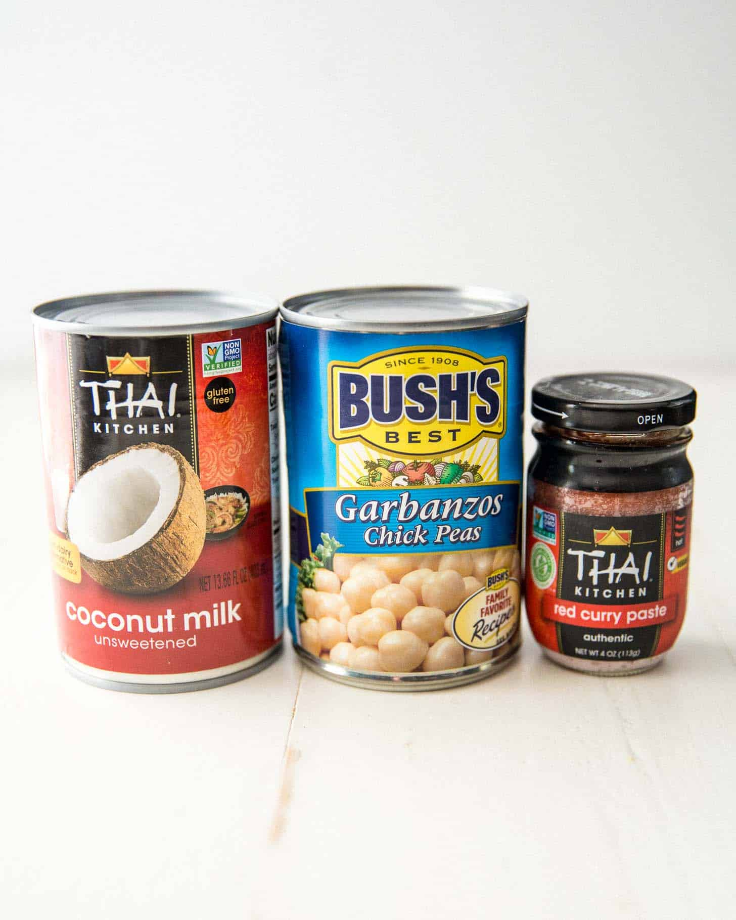cans of chick peas, coconut milk and red curry paste on a white table