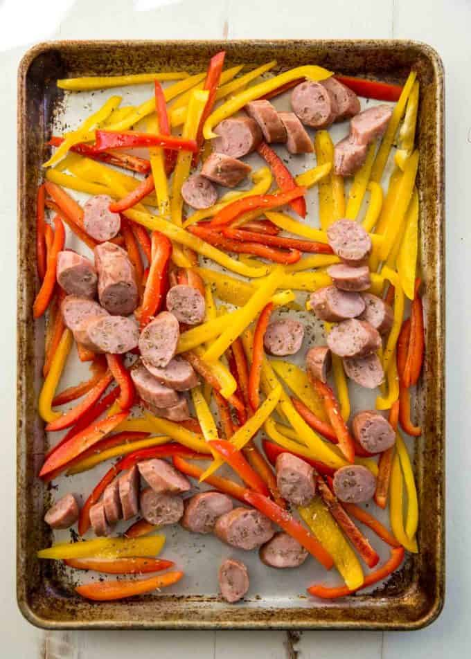 uncooked sausage and peppers on a sheet pan