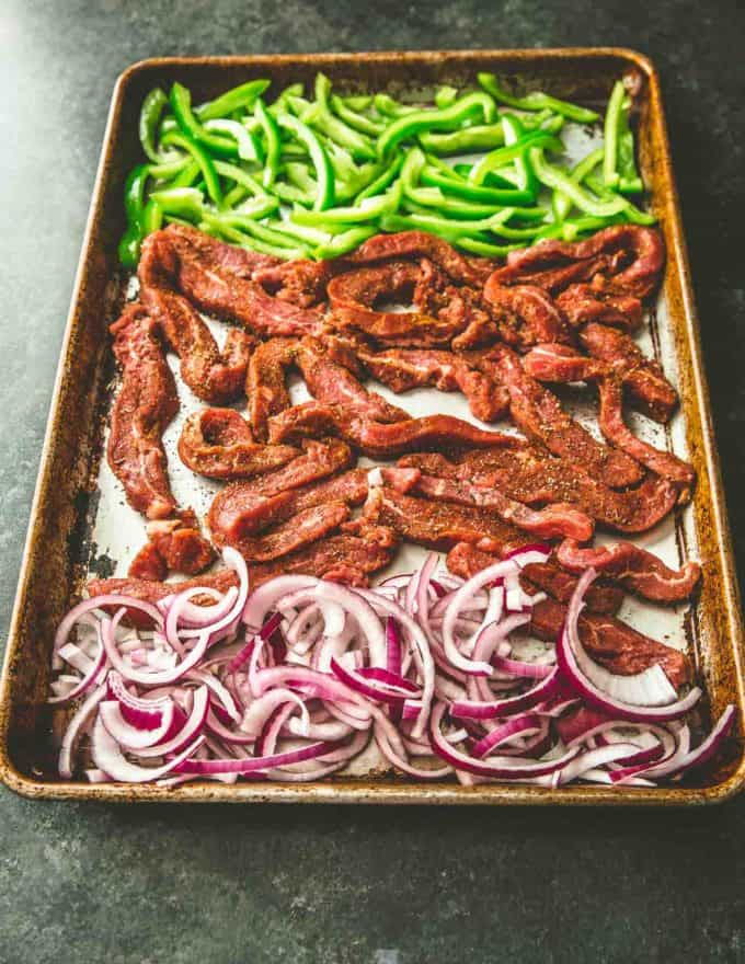 uncooked steak, onions and peppers on a sheet pan