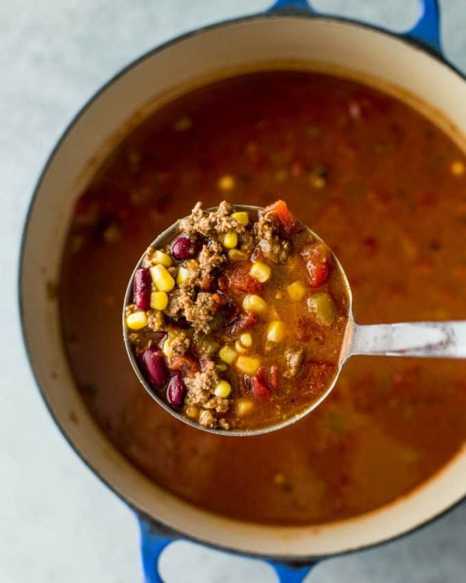 a spoonful of taco soup above a dutch oven