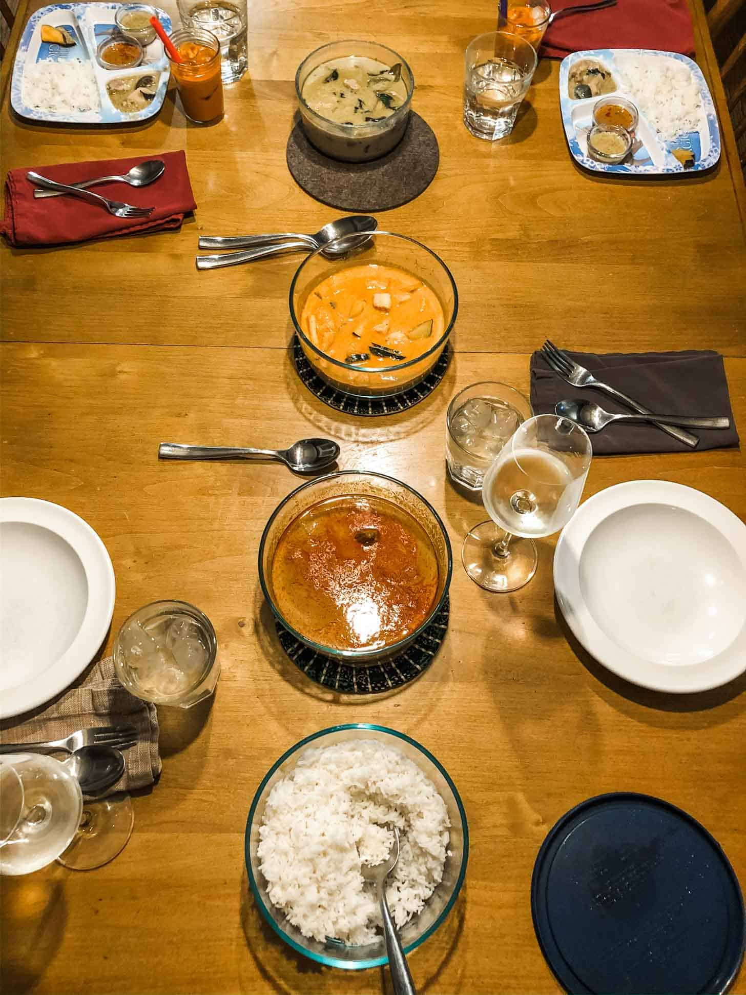 3 bowls of thai curries and rice on a table