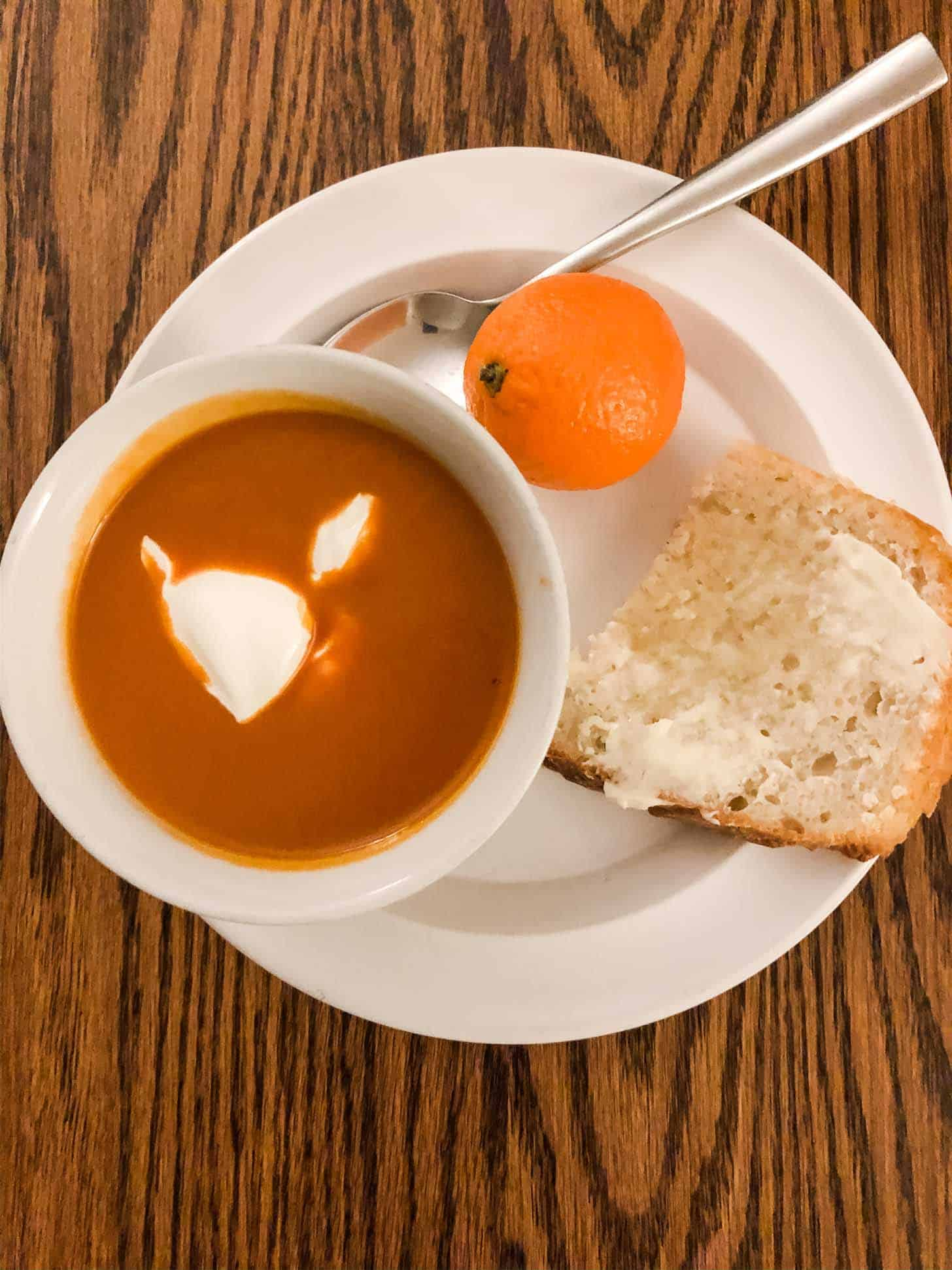 soup in a bowl with toast on a plate