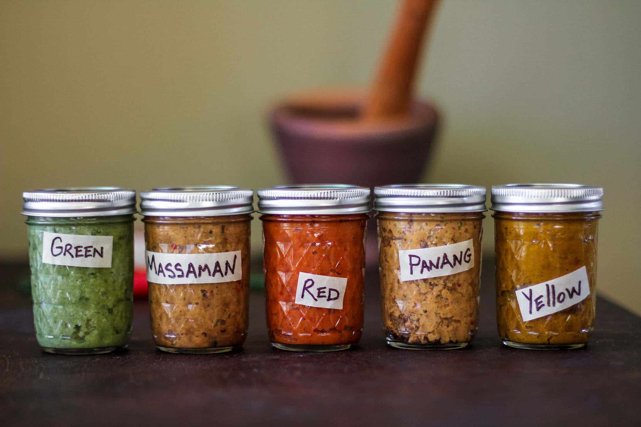 Mason jars of curries -- green, massaman, red, panang and yellow
