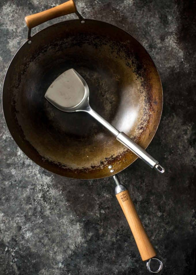a wok and a spatula on a grey countertop
