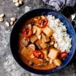Thai Massaman Curry over rice in a blue bowl