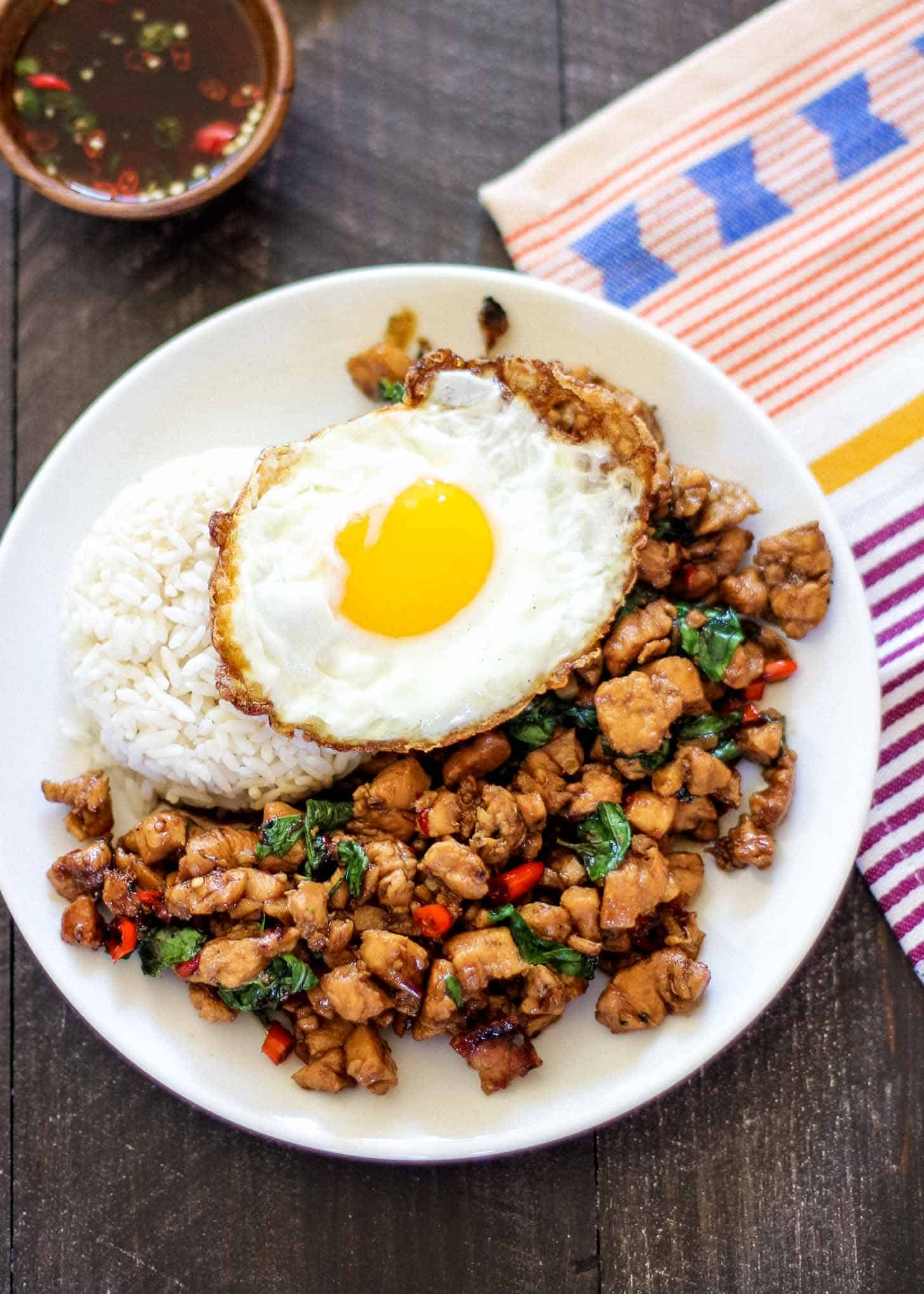 thai basil chicken topped with a fried egg on a white plate