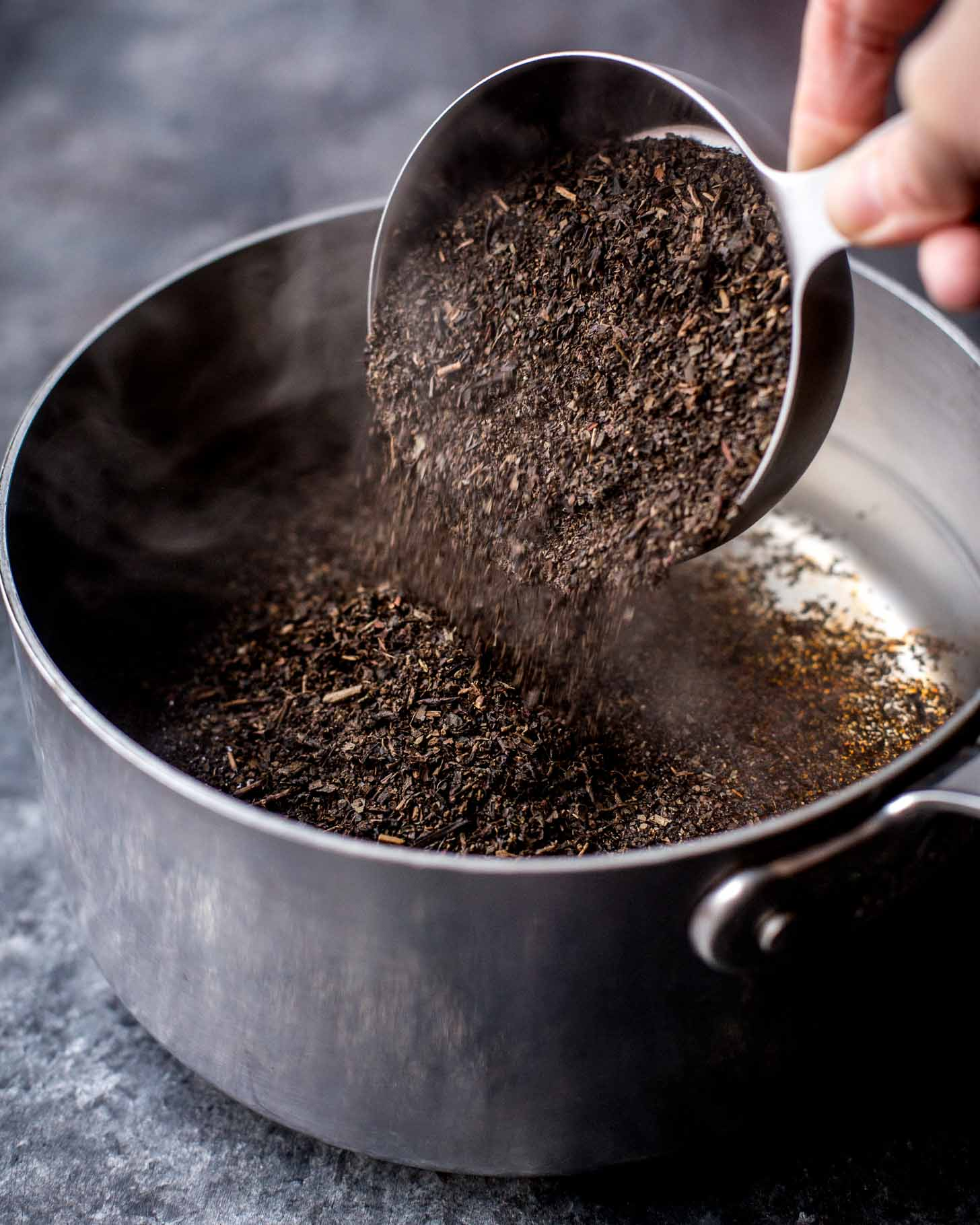 adding thai tea mix to water in a pan