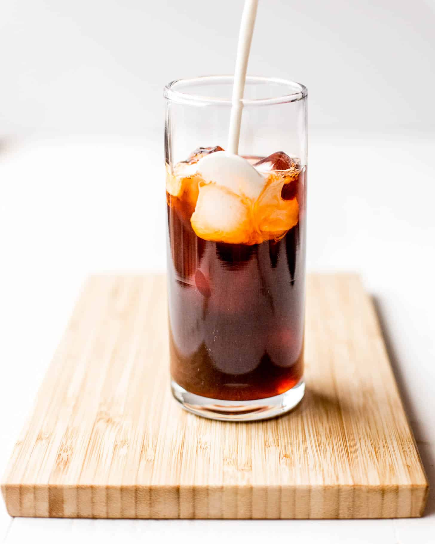 adding milk to iced tea in a glass