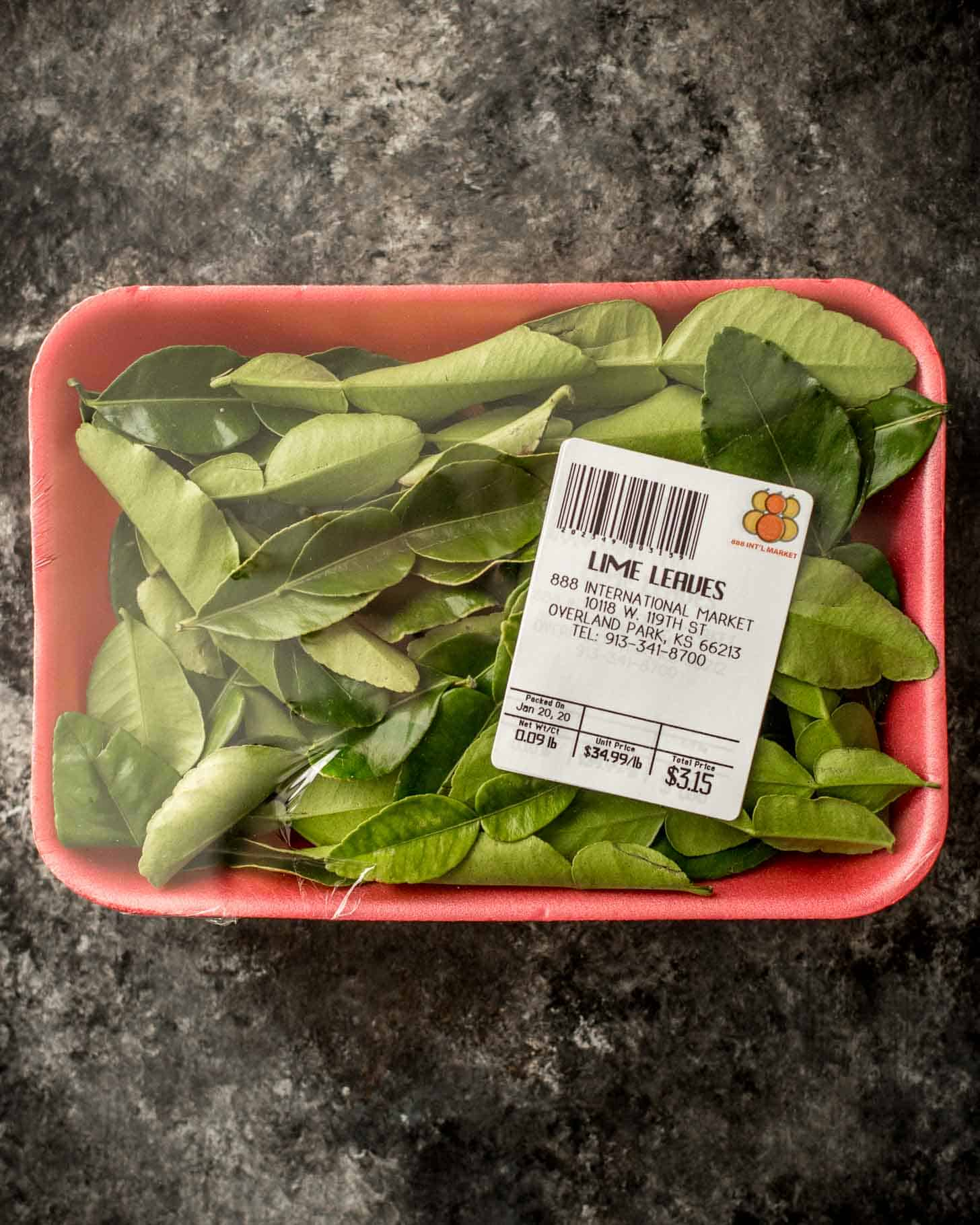 kaffir lime leaves in a package on a grey countertop