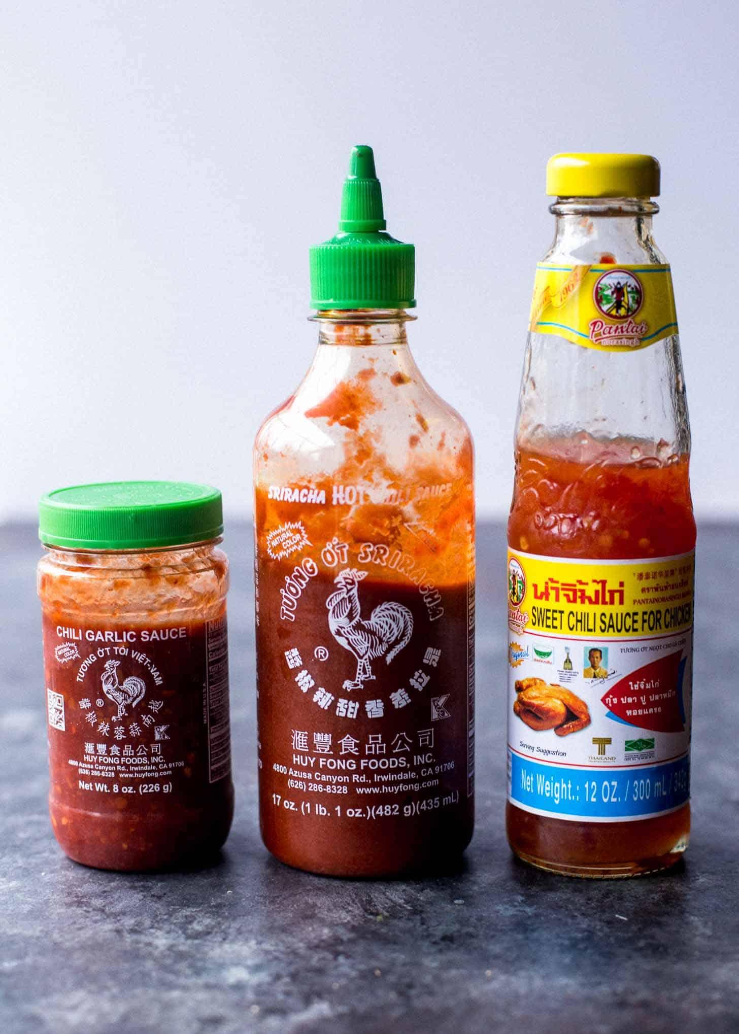 Bottles of Thai hot sauce on a grey countertop