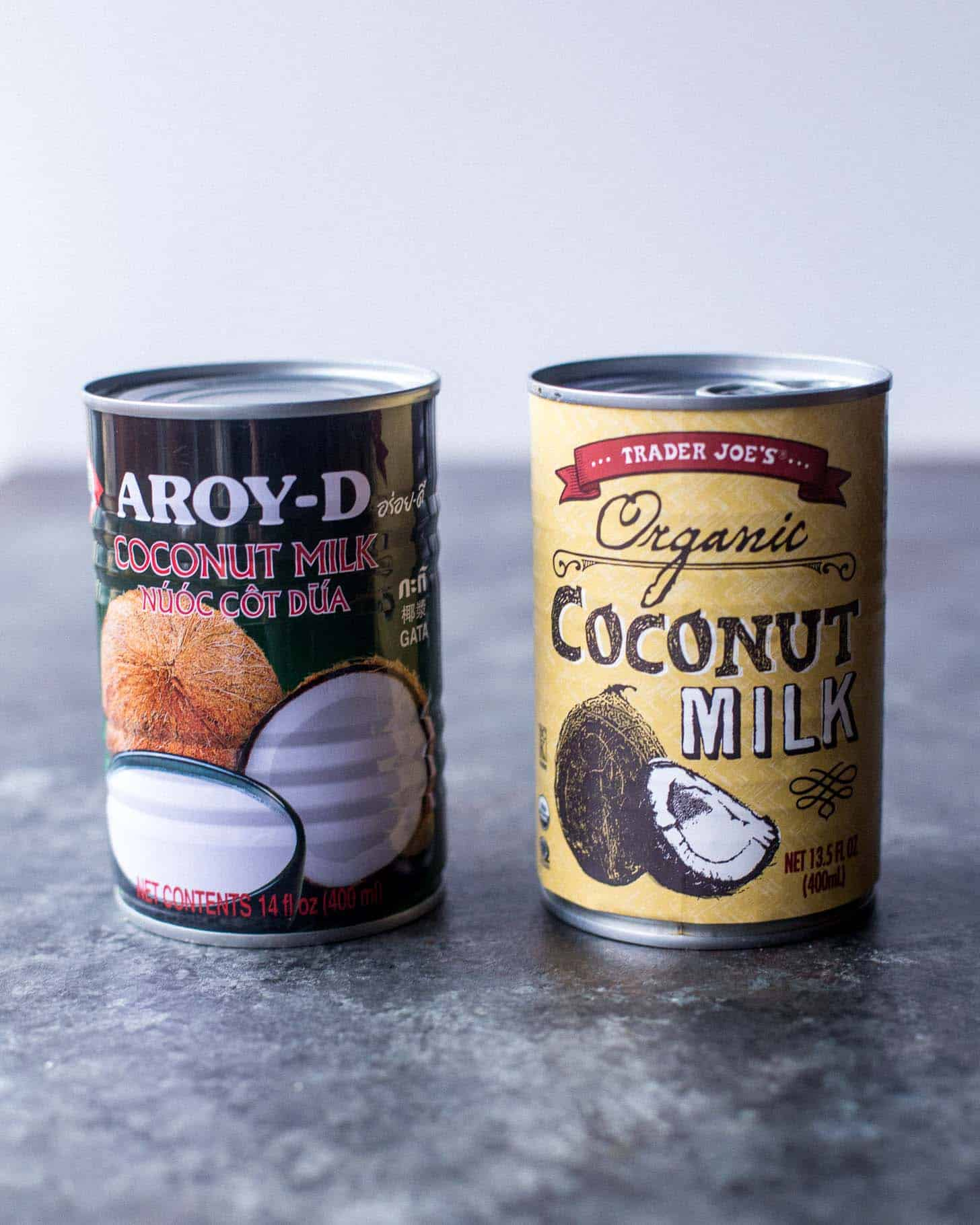 2 cans of coconut milk on a grey countertop