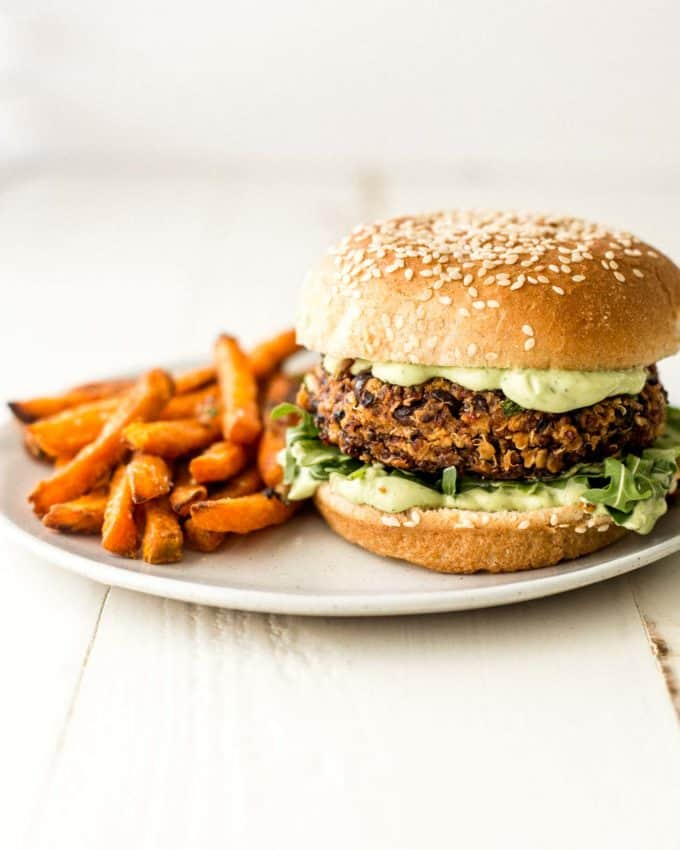 black bean and quinoa veggie burger on a white plate with sweet potato fries