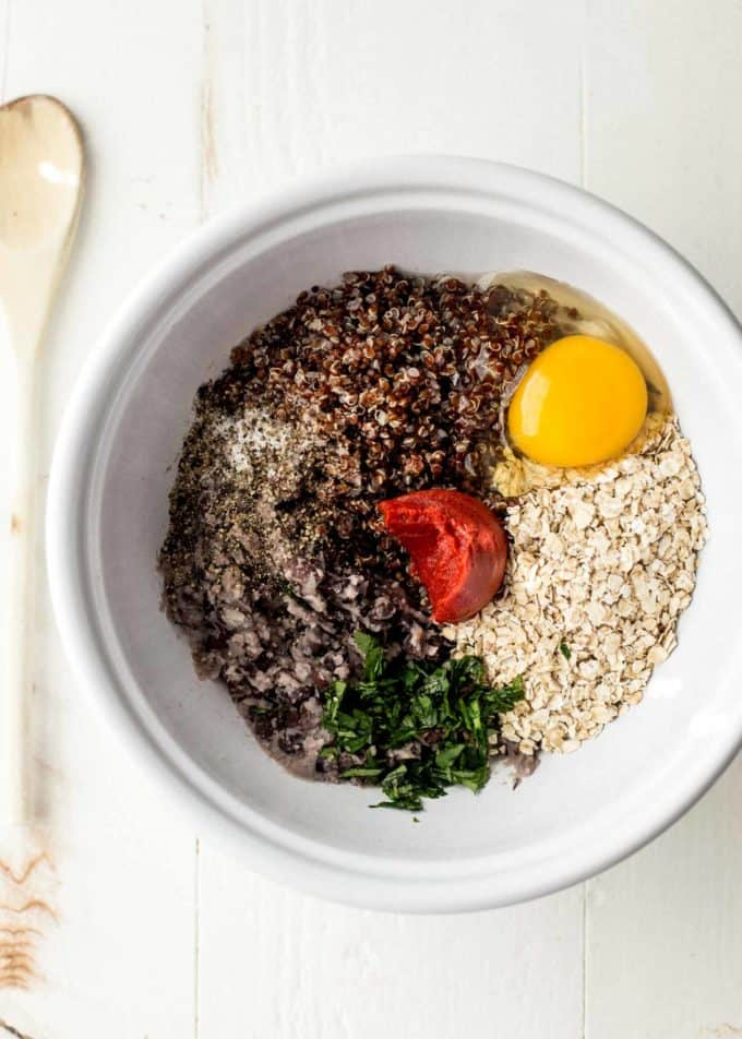 black beans, spices, tomato sauce, quinoa and egg in a white bowl on a white table