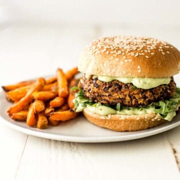 black bean and quinoa veggie burger on a white plate next to sweet potato fries