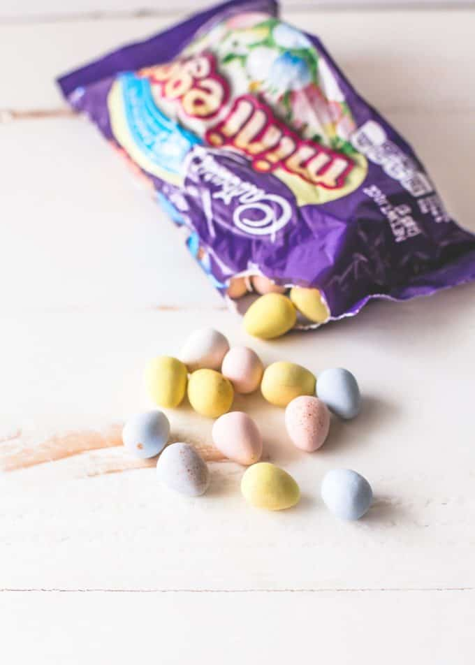 Cadbury mini eggs spilling out of a bag on a white table