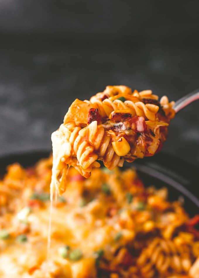 a spoonful of chicken enchilada pasta above a skillet full of casserole