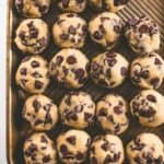 chocolate chip cookie dough in balls on a sheet pan