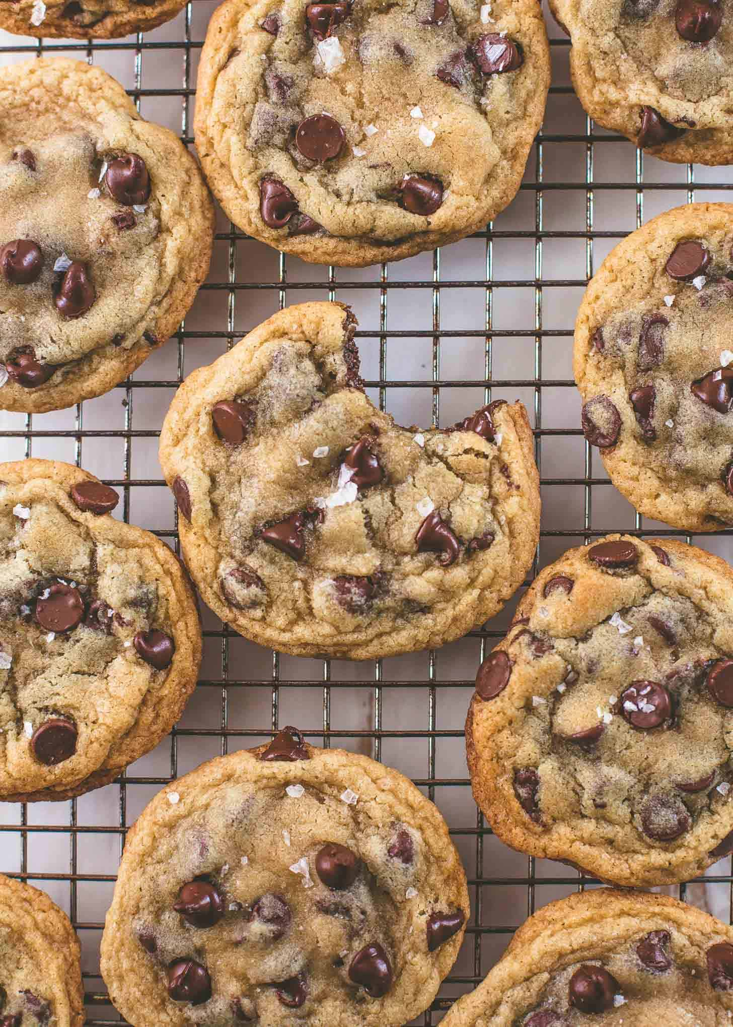 chocolate chip cookies on a cooling rack, one with a bite taken out of it