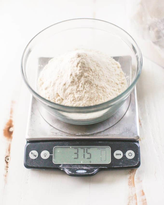 weighing flour for cookies on a kitchen scale