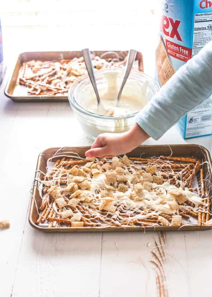 sprinkling chex cereal onto pretzels and almond bark on sheet pans