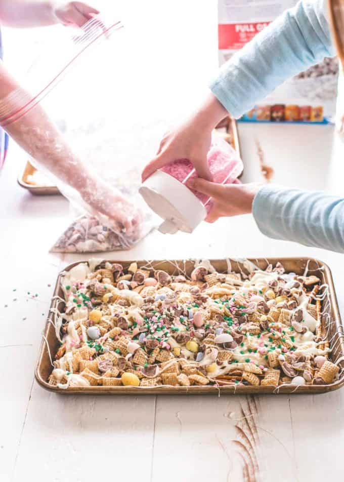 putting toppings on Easter Egg Crunch Bark on a sheet pan