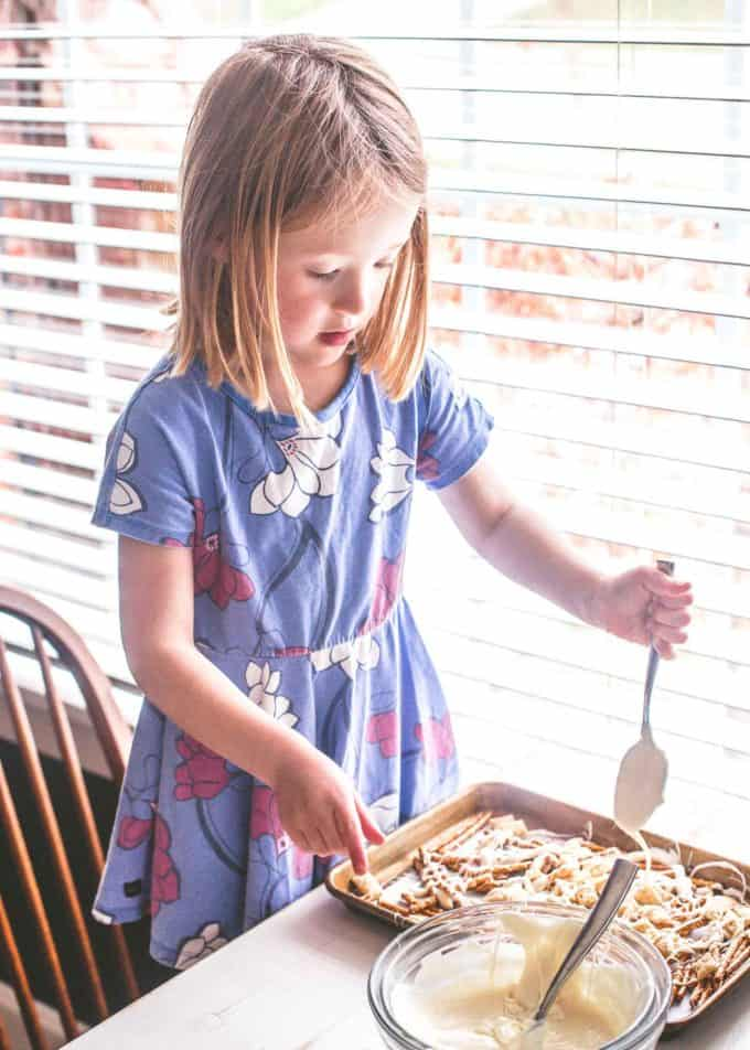 a young girl in a purple floral dress drizzles white chocolate over Easter Egg Crunch Bark