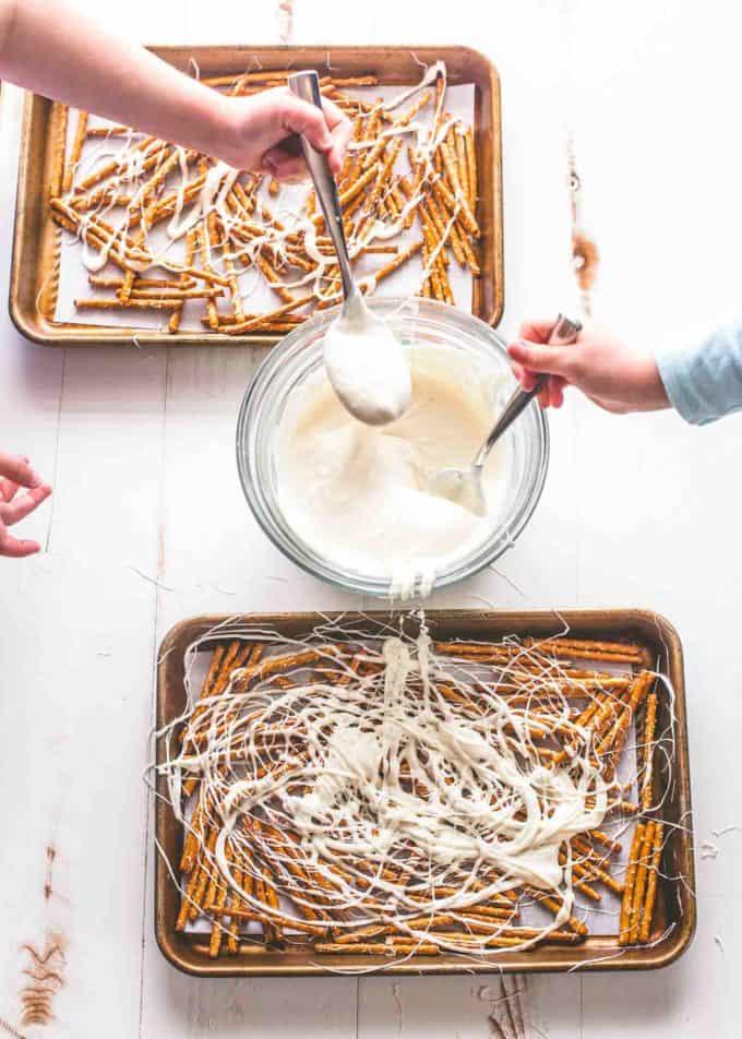 drizzling Yogurt on pretzels on parchment lined sheet pans
