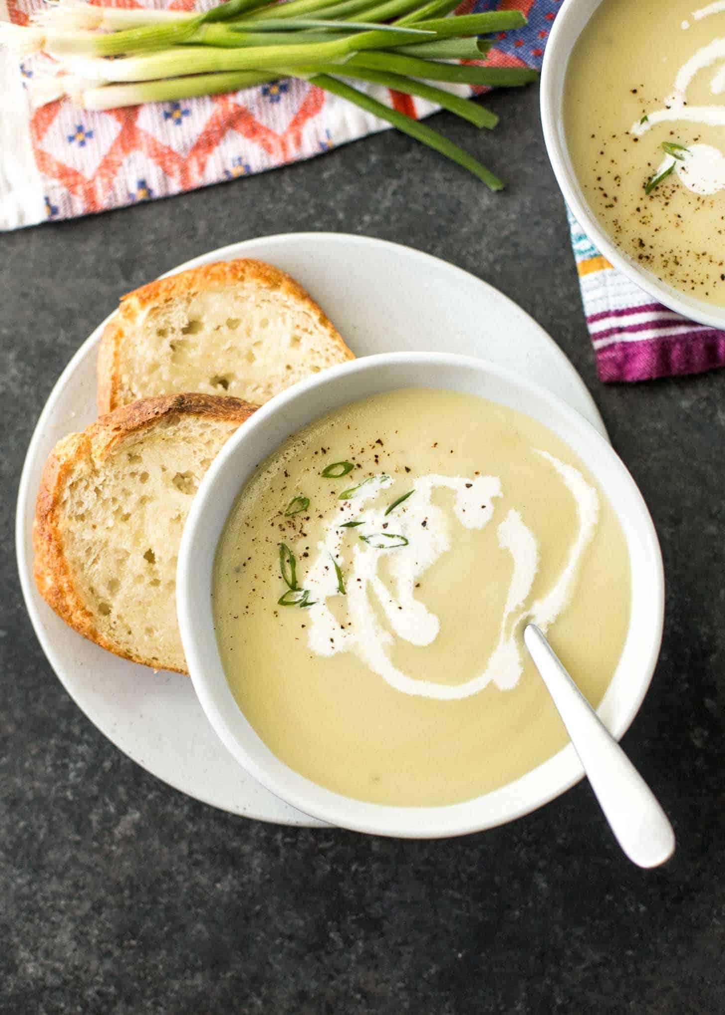 Instant Pot Potato Leek Soup in a white bowl, next to crusty bread