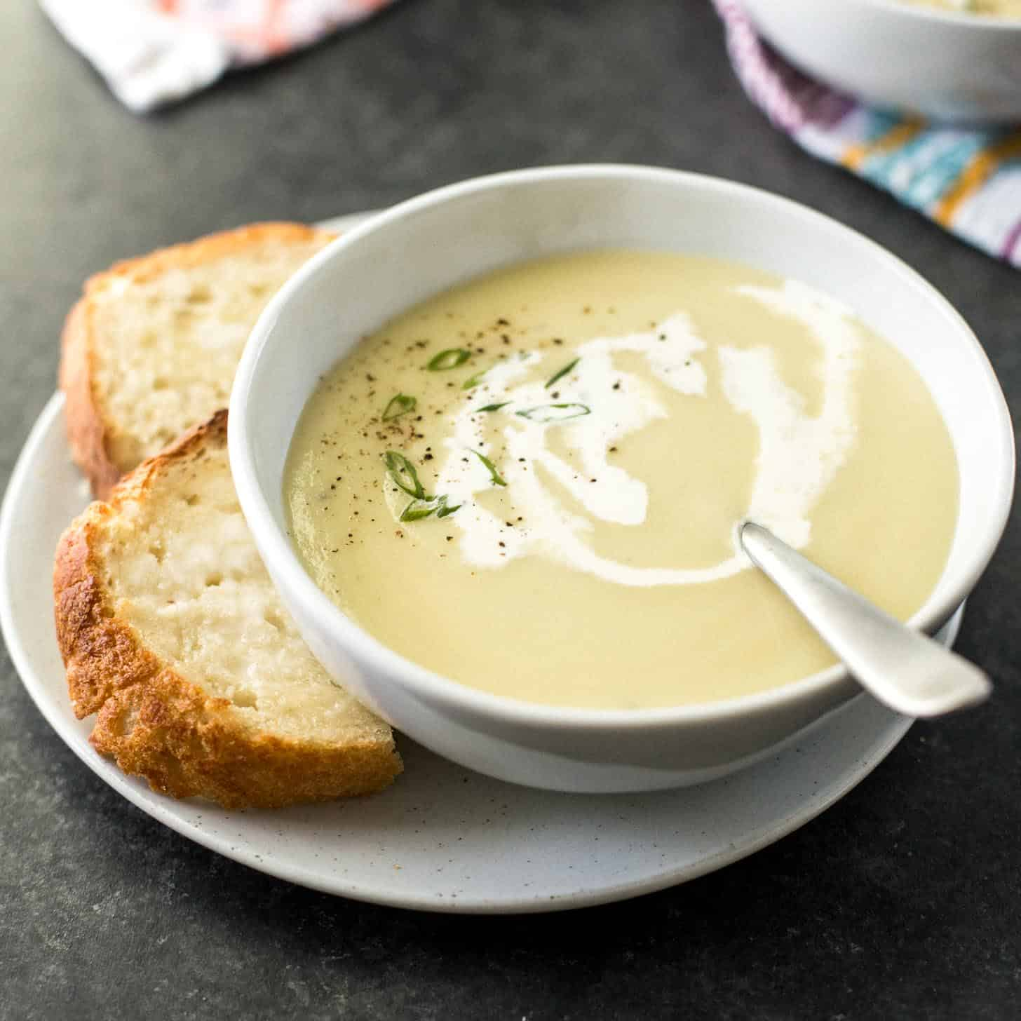 Instant Pot potato leek soup in a white bowl next to sliced crusty bread
