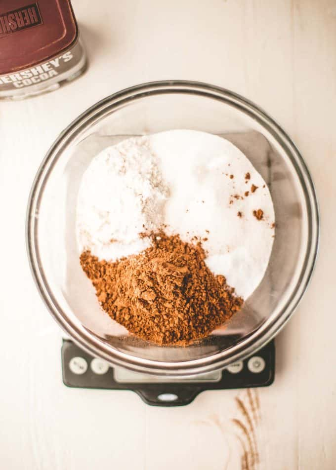 dry ingredients for chocolate cake in a bowl on a kitchen scale