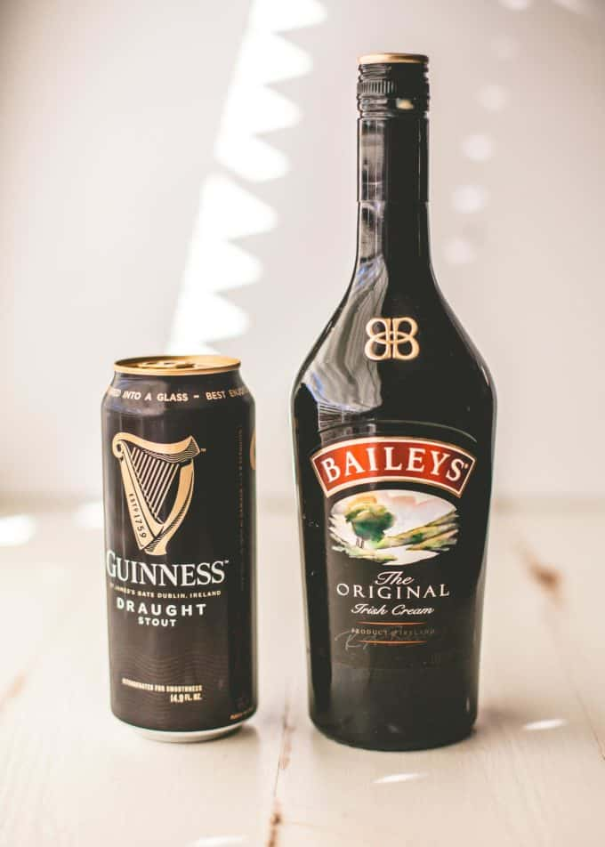 a can of Guinness next to a bottle of Bailey's on a white tabletop