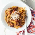 puttanesca with beef over pasta in a white bowl