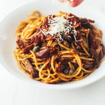 slow cooker beef puttanesca over pasta in a white bowl