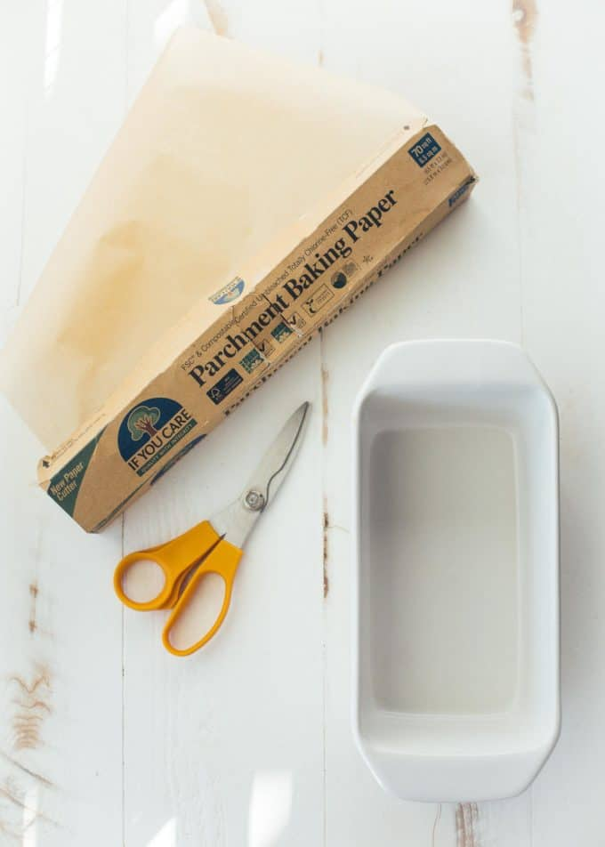 a roll of parchment paper and scissors on a white table next to a loaf pan