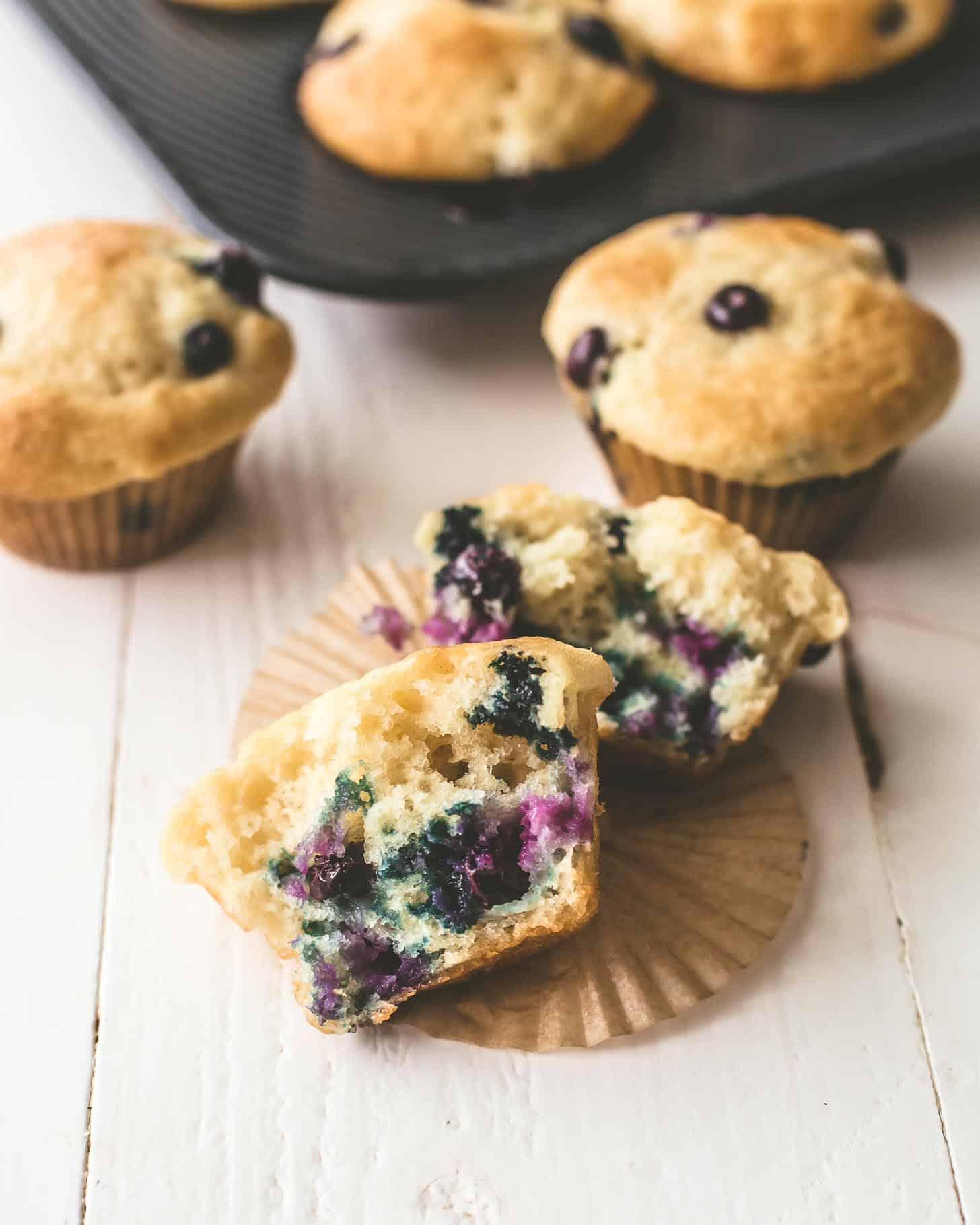 Blueberry Yogurt Muffins on a white table. One muffin is broken in half on a muffin wrapper.