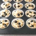 blueberry yogurt muffin batter in a muffin tin
