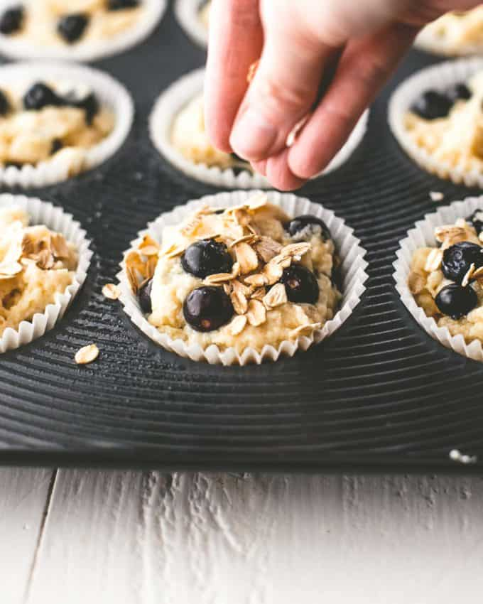 sprinkling oats onto blueberry muffin batter in a muffin tin