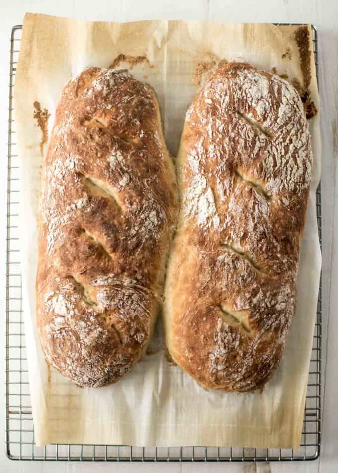 2 loaves of No Knead French Bread on parchment paper on a cooling rack