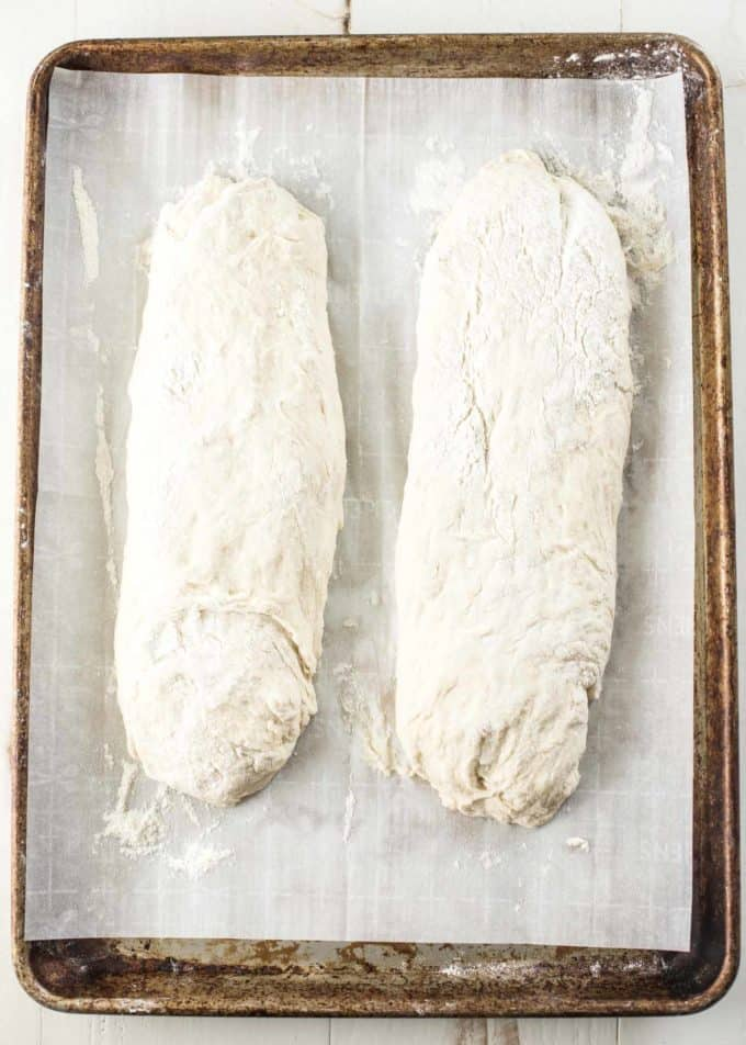 2 loaves of unbaked No Knead French Bread on a parchment lined sheet pan