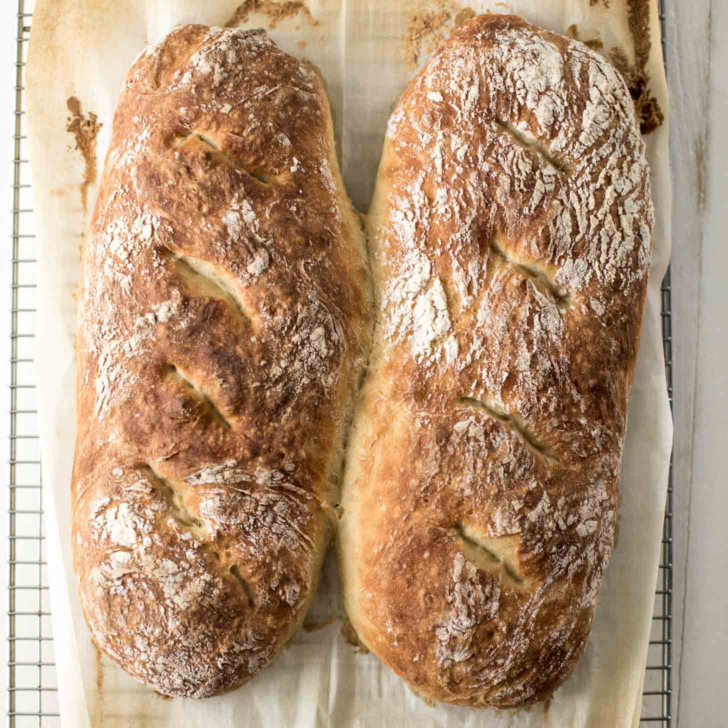 2 loaves of No Knead French Bread on parchment on a cooling rack