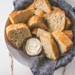 sliced no-knead everyday bread in a bowl with a blue towel with a small ramekin of butter