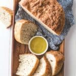 sliced no knead everyday bread on a wooden tray with a blue towel draped over the corner