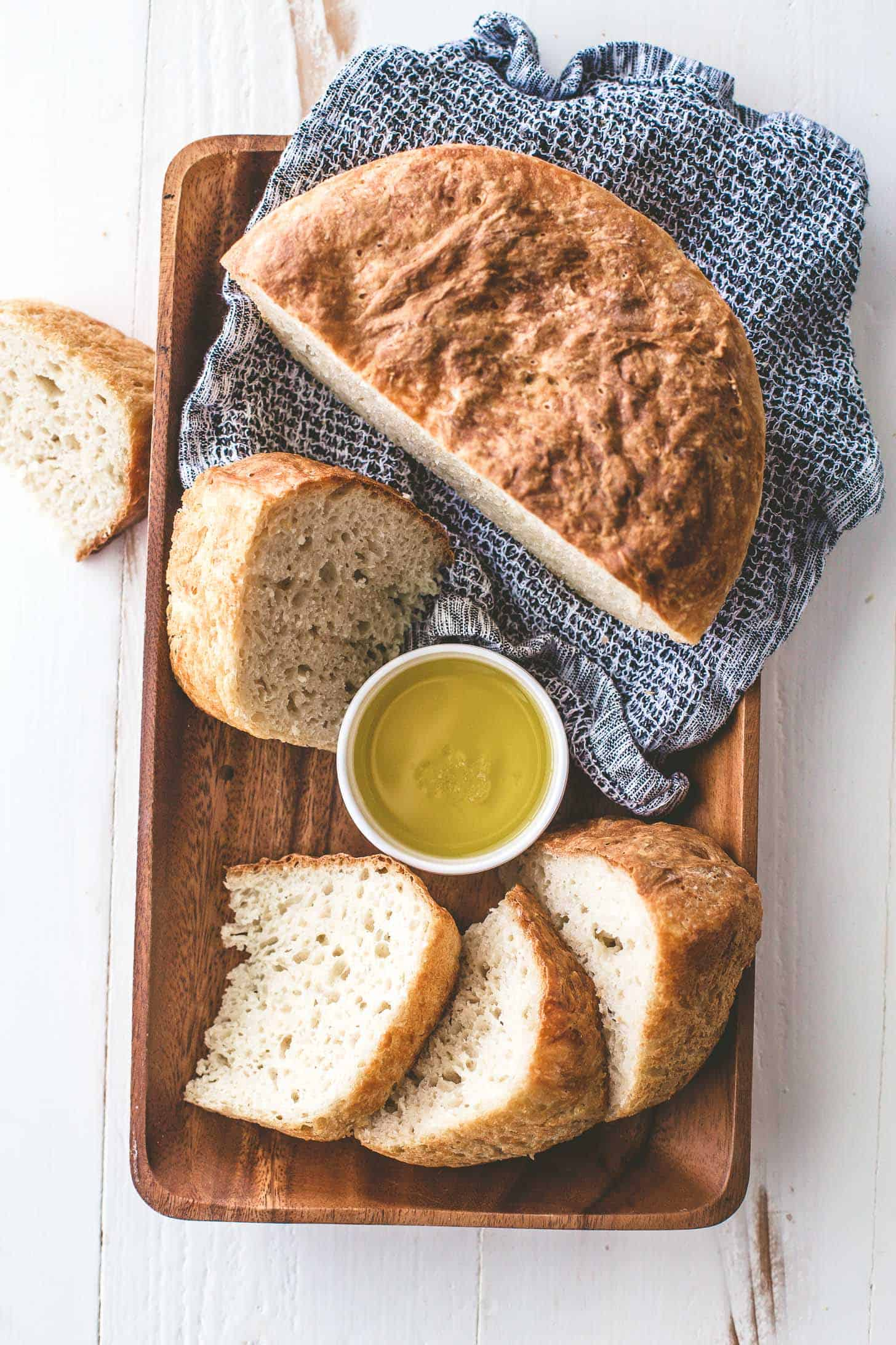 no knead everyday bread sliced and resting on a wooden tray with a blue towel draped over the corner