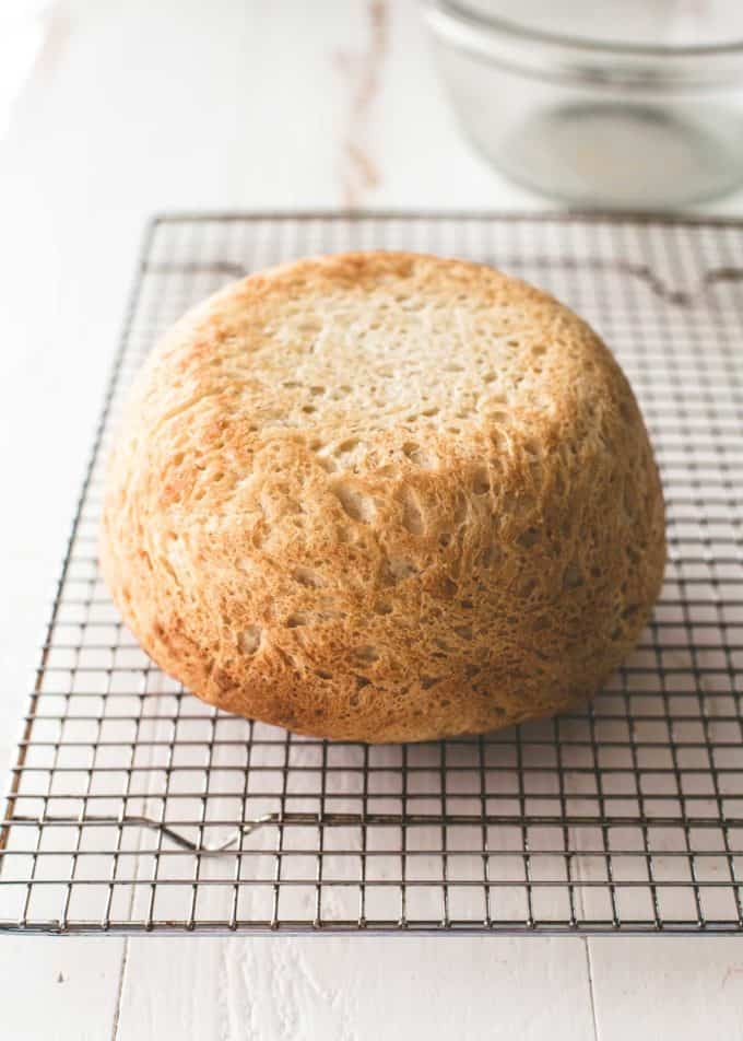 a round loaf of no knead everyday bread on a cooling rack
