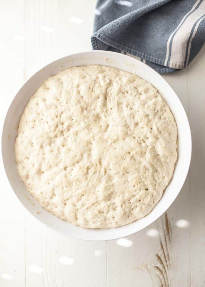 no knead everyday bread dough after rising in a white bowl