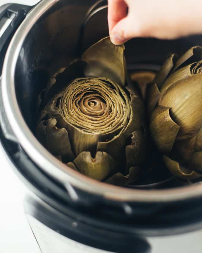 pulling a leaf off of a steamed artichoke in an instant pot